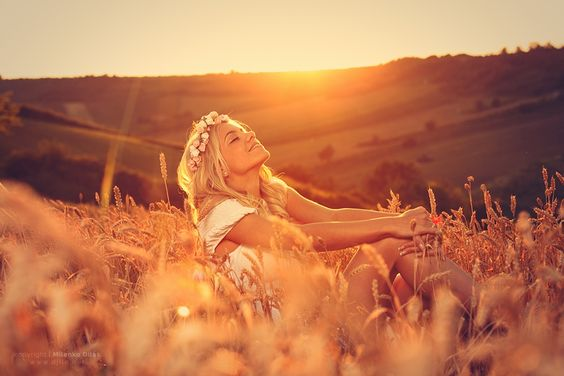 Beautiful young woman sitting in wheat and enjoy